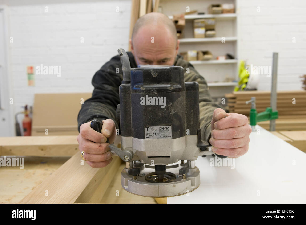 craftsmen work in a woodworking factory preparing high quality furnishing using both traditional and modern, industrial - Stock Image