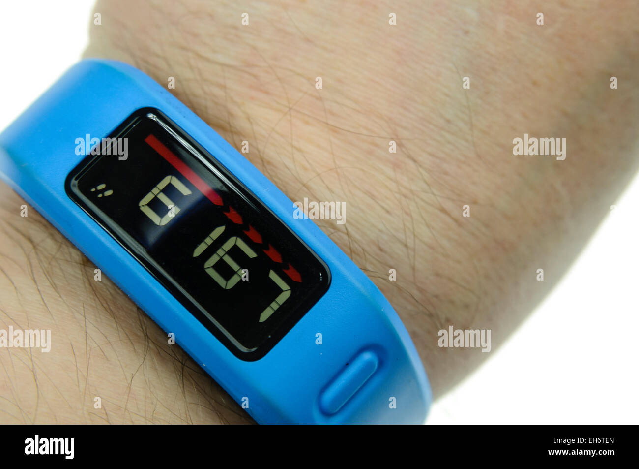 A man checks his daily number of steps on a a Garmin Vivofit fitness band on his wrist - Stock Image