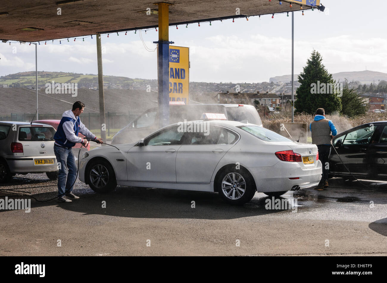 Men Wash Cars With Power Washers At A Euro Car Wash Stock Photo