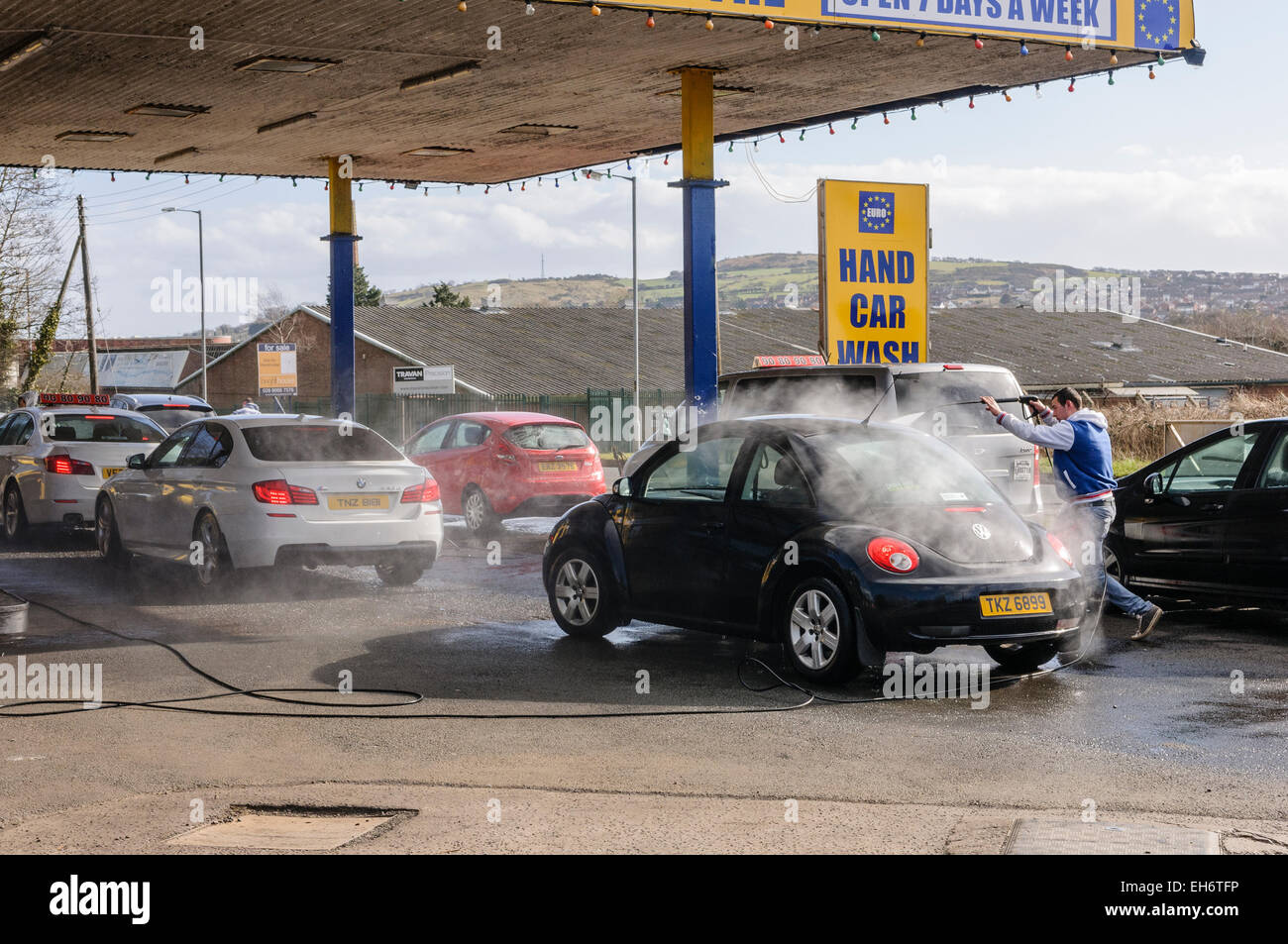A Man Washes Cars With A Power Washer At A Euro Car Wash Stock