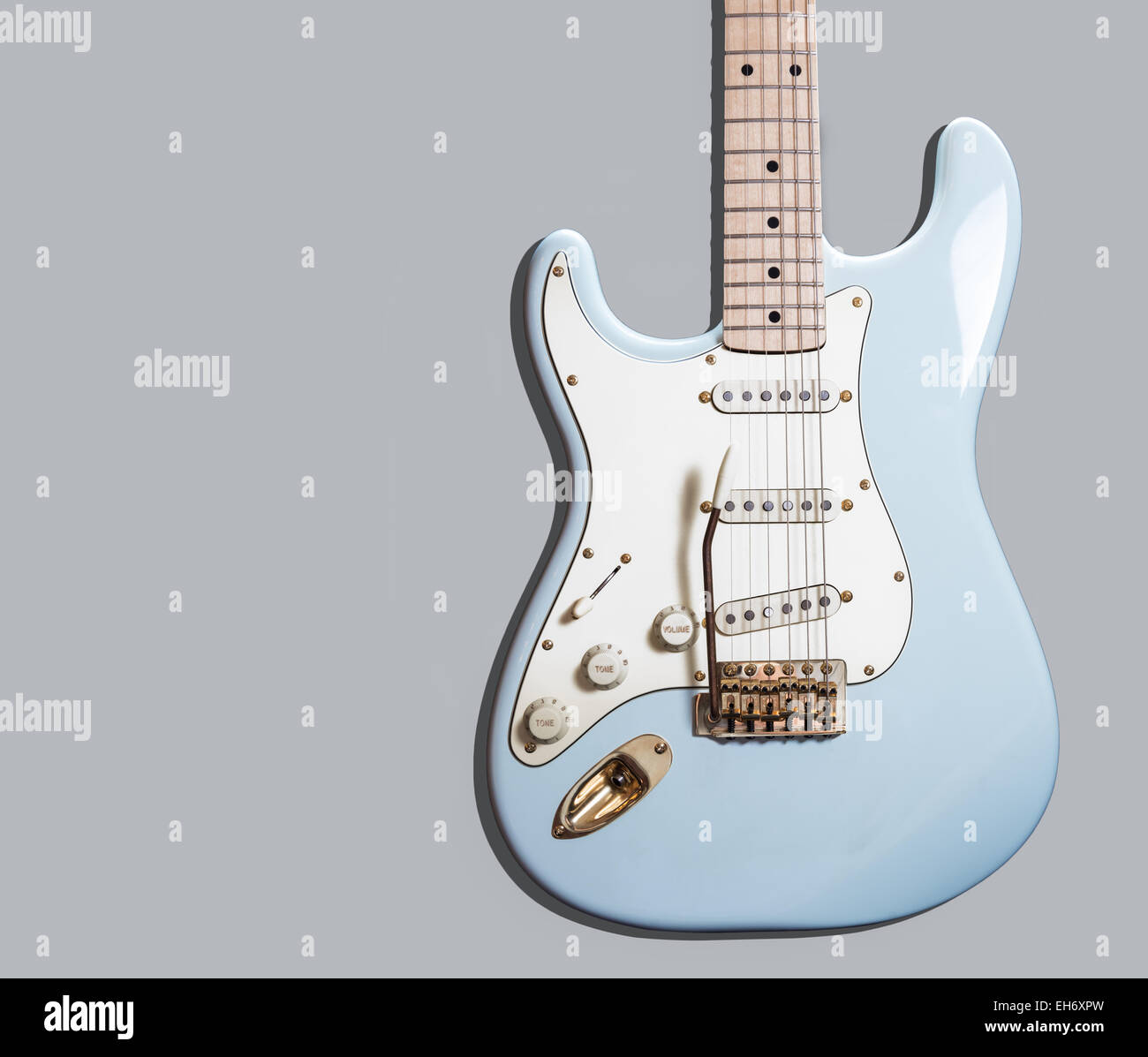 A pale blue electric guitar against a gray background Stock Photo