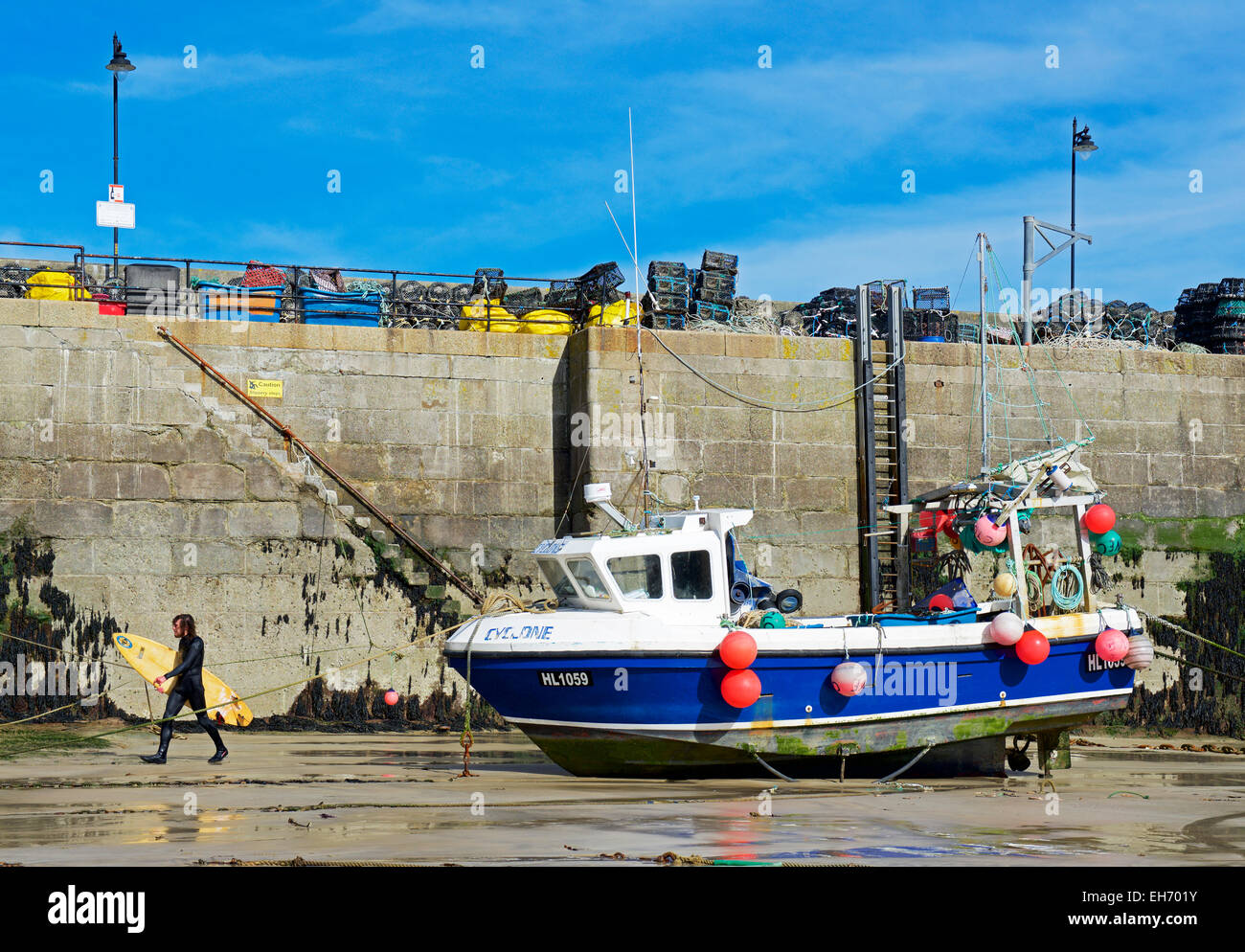 Surfer walking past a fishing boat in harbour, Newquay, Cornwall, England UK - Stock Image