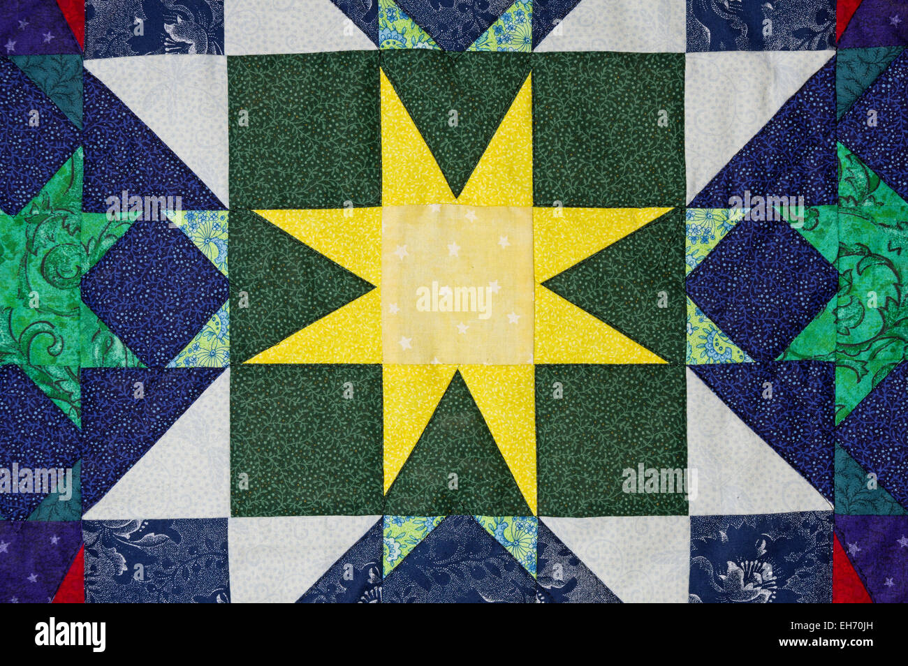 hand made quilt detail with colorful patterned cloth - Stock Image