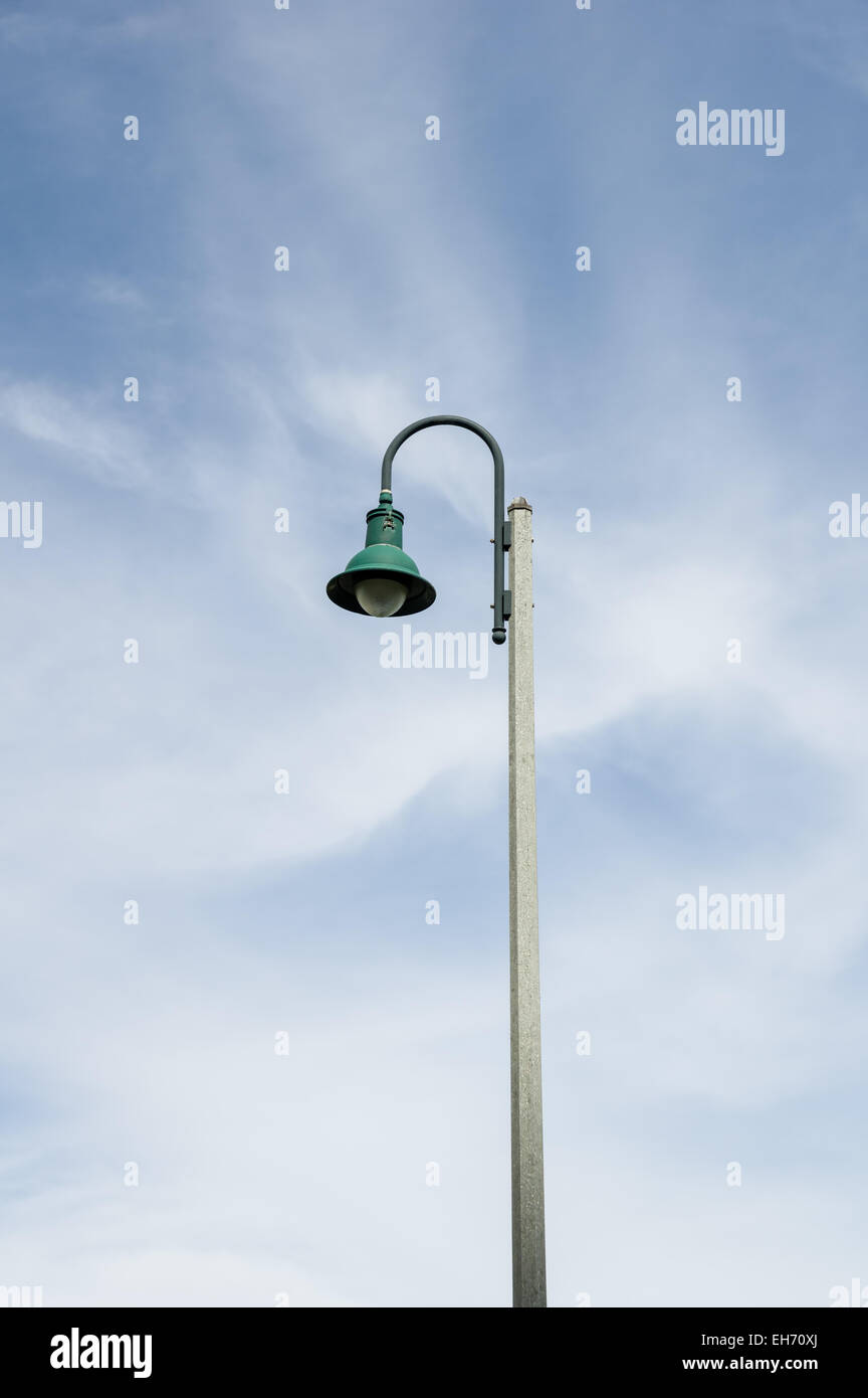 green bent down streetlamp with partly cloudy sky background - Stock Image