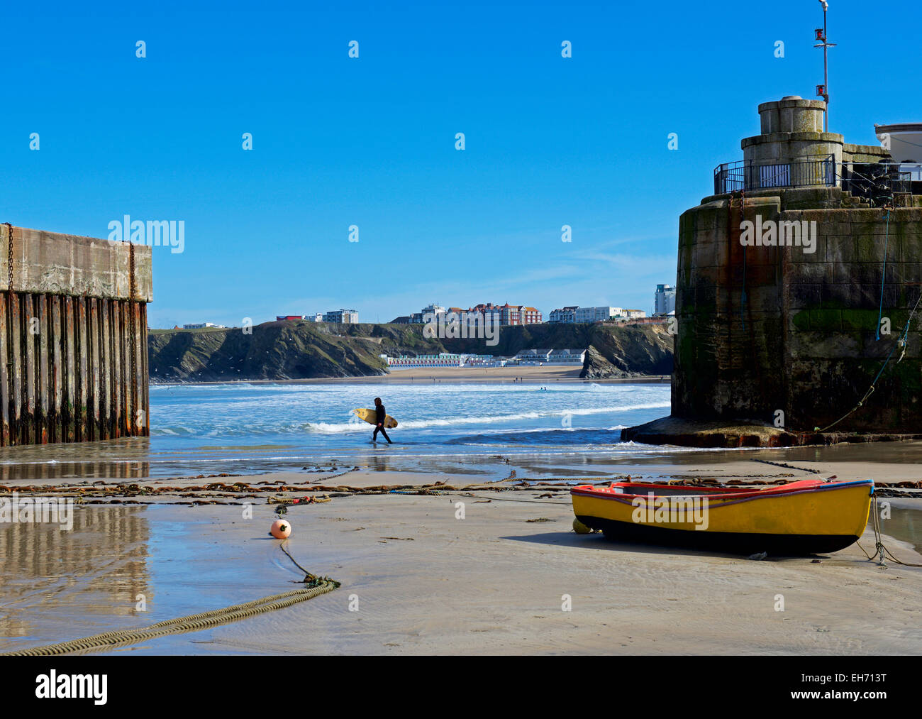 Surfer walking past the harbour, Newquay, Cornwall, England UK - Stock Image