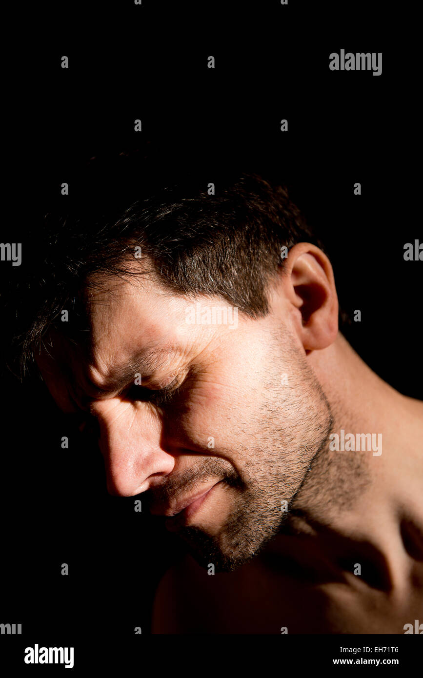 Portrait of a tearful, unshaven man with his eyes closed and against a black background. - Stock Image