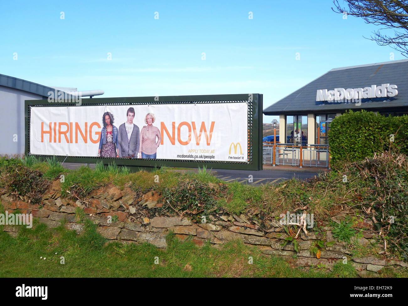 A ' Hiring Now ' sign outside a Mcdonalds restaurant in Cornwall, UK - Stock Image
