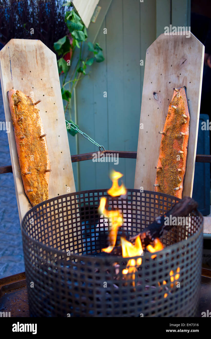 Salmon fillets pegged out on boards alongside a brazier to smoke as it was traditionally done in the Middle Ages. - Stock Image