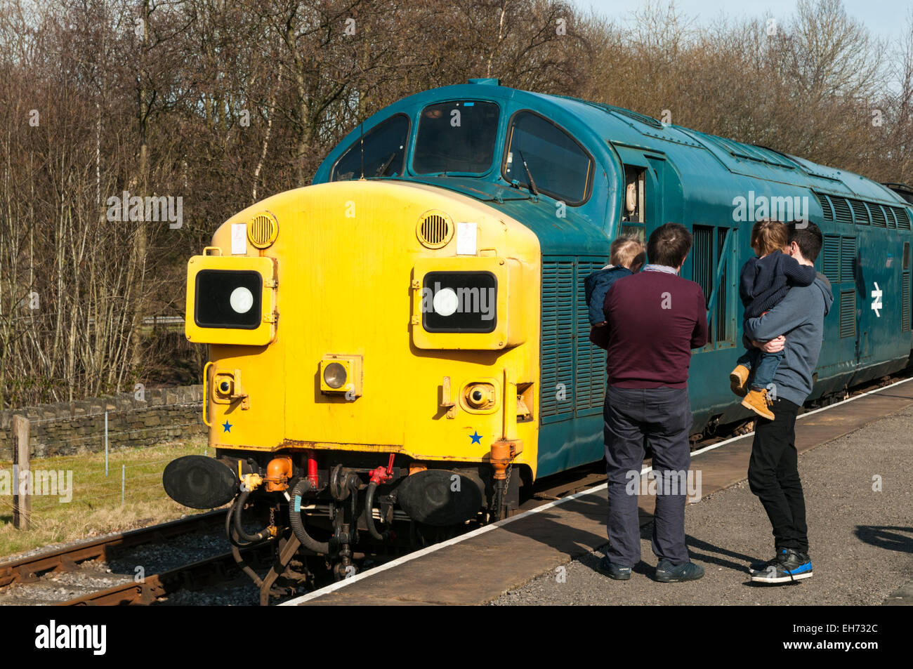 Two Dads carrying their toddlers looking at a 1980s class 37 diesel loco at Rawtenstall on the East Lancs Railway - Stock Image
