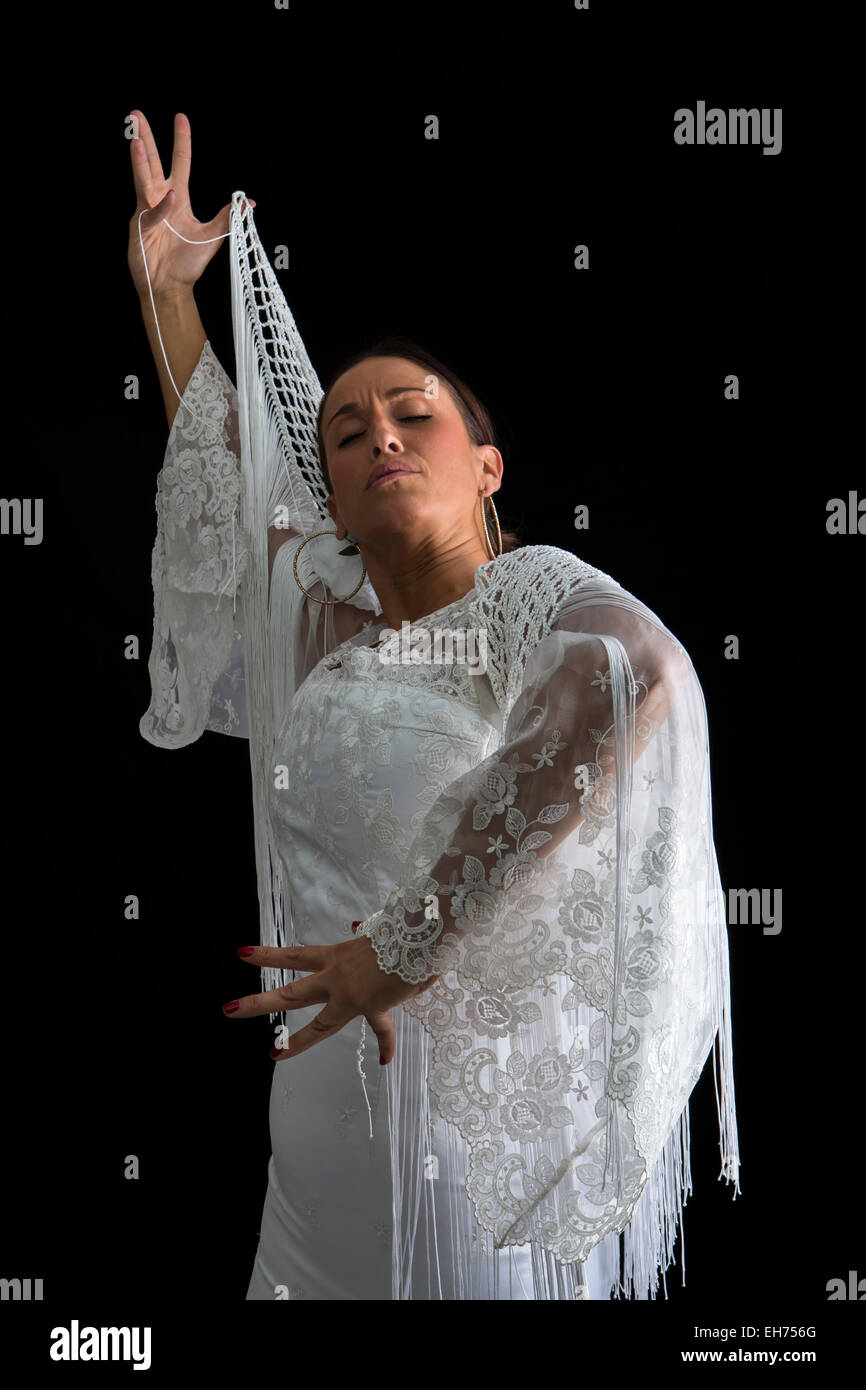 Flamenco dancer backs with white dress and hands crossed up  on black background - Stock Image