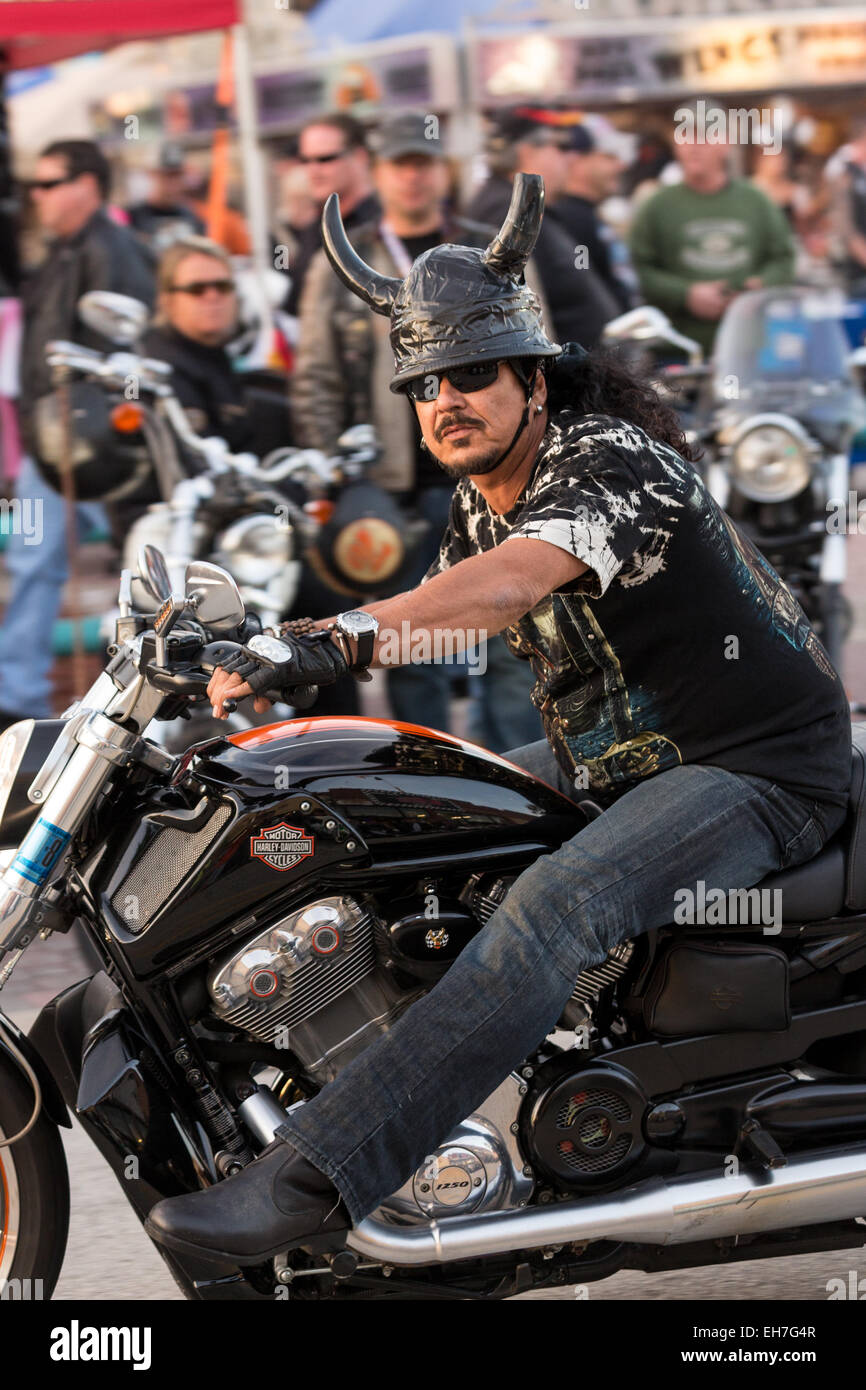 A leather clad biker with animal horns on his helmet cruises down Main Street during the 74th Annual Daytona Bike Stock Photo
