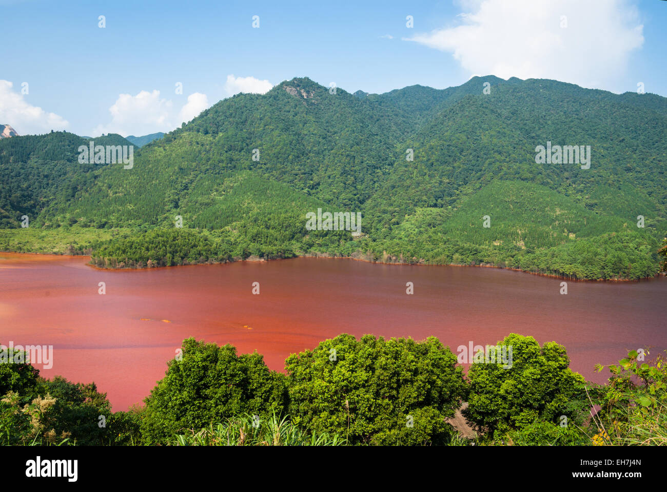 Lake containing acid mine drainage from the Dabaoshan Mine in Guangdong, China - Stock Image
