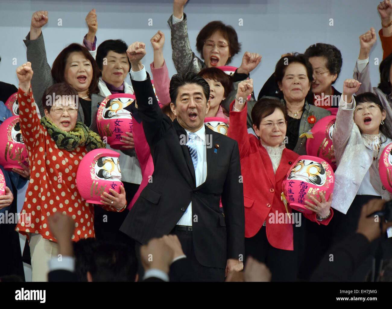 Tokyo, Japan. 8th Mar, 2015. Japan's Prime Minister Shinzo Abe, center, leads the fellow party members to raise - Stock Image