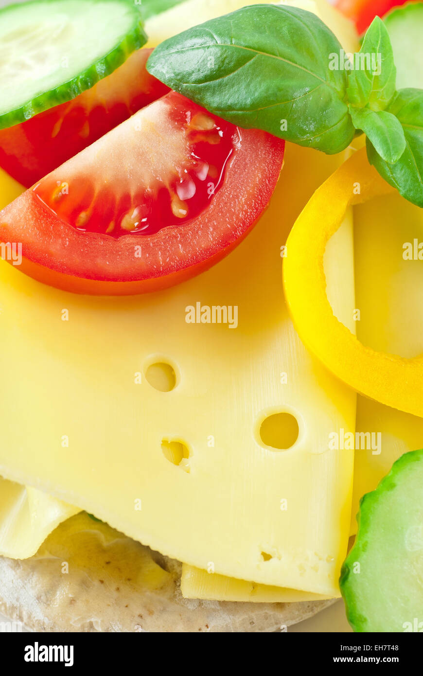 Cheese sandwich with tomato, yellow bell pepper and cucumber. - Stock Image