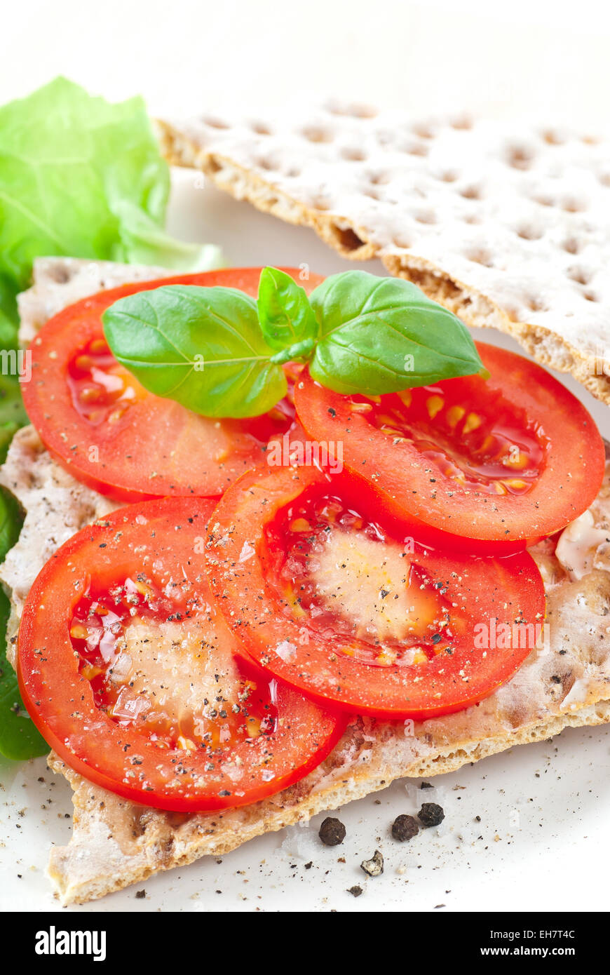Crispbread with tomato slices. Spiced with sea salt and black pepper. - Stock Image