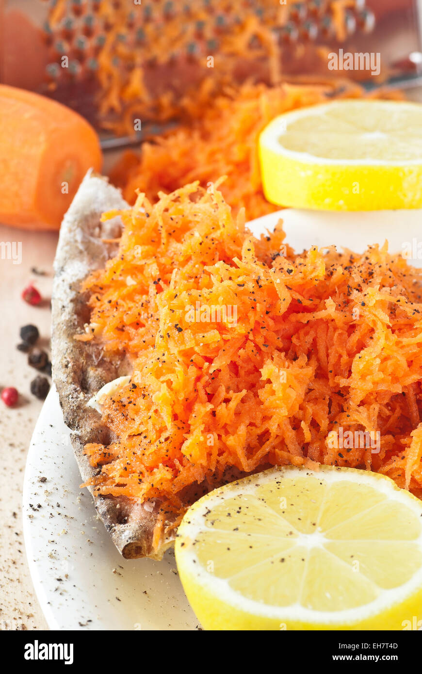 Crispbread with grated carrot.  Seasoned with lemon and black pepper. - Stock Image