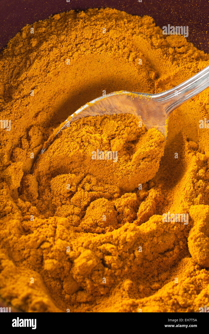 A spoon ful of ground turmeric. - Stock Image