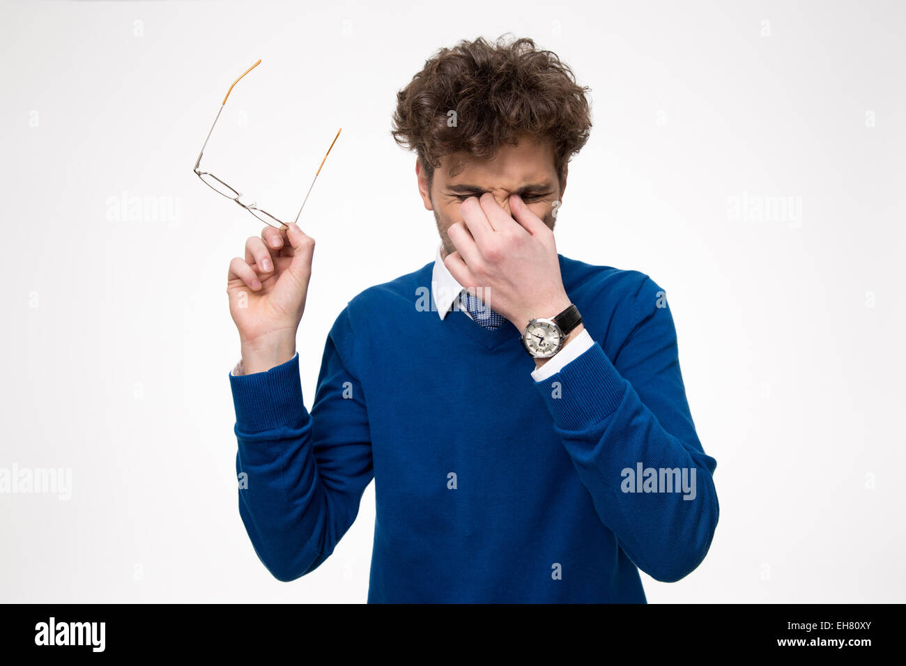 Young businessman rubbing his eyes over white background - Stock Image
