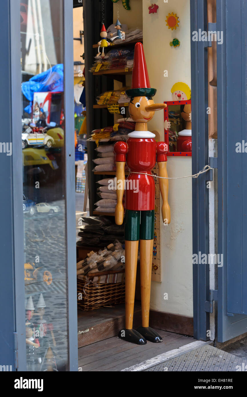 A tall wooden Pinocchio character in red outfit, Rome, Italy. - Stock Image