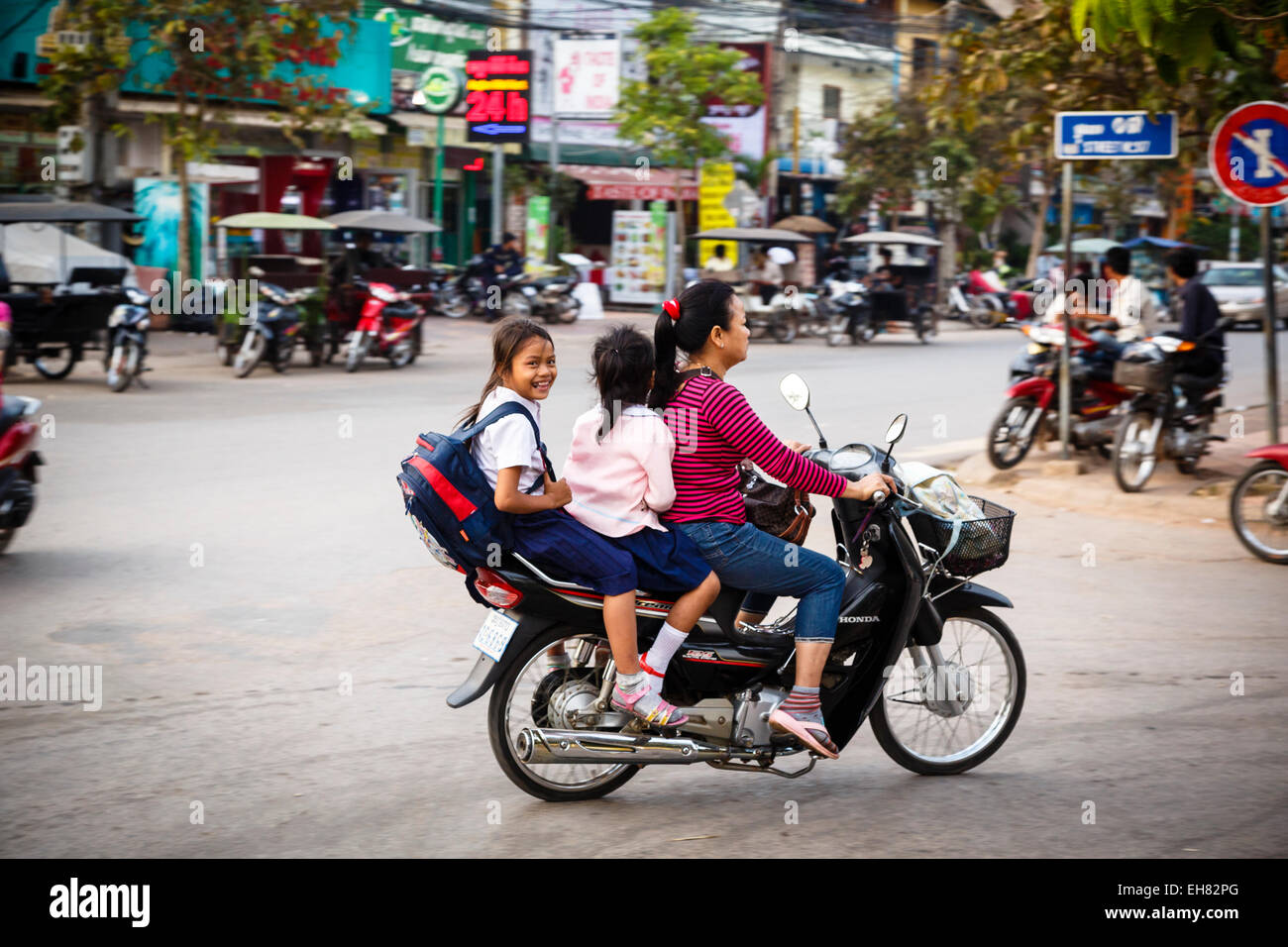 Mother and daughters riding a scooter, Siem Reap, Cambodia, Indochina, Southeast Asia, Asia - Stock Image