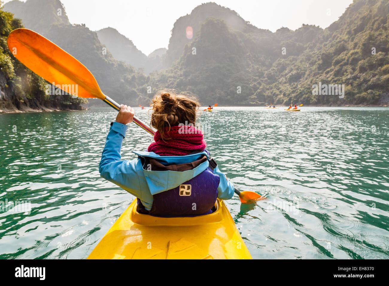 Woman kayaking at Halong Bay, Vietnam, Indochina, Southeast Asia, Asia - Stock Image
