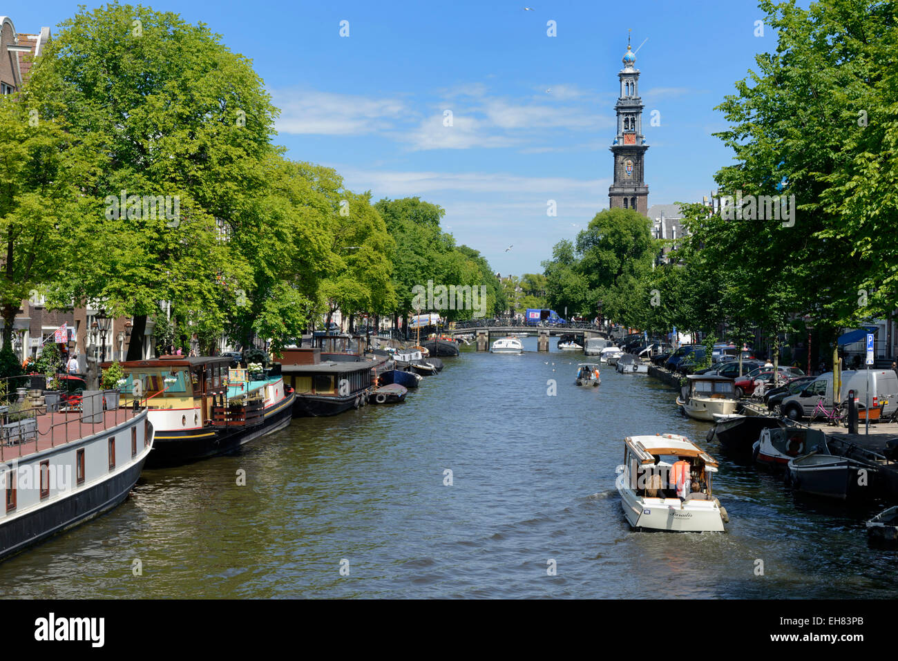 View along Prinsengracht canal, looking towards Westerkerk church, Amsterdam, North Holland, Netherlands, Europe - Stock Image