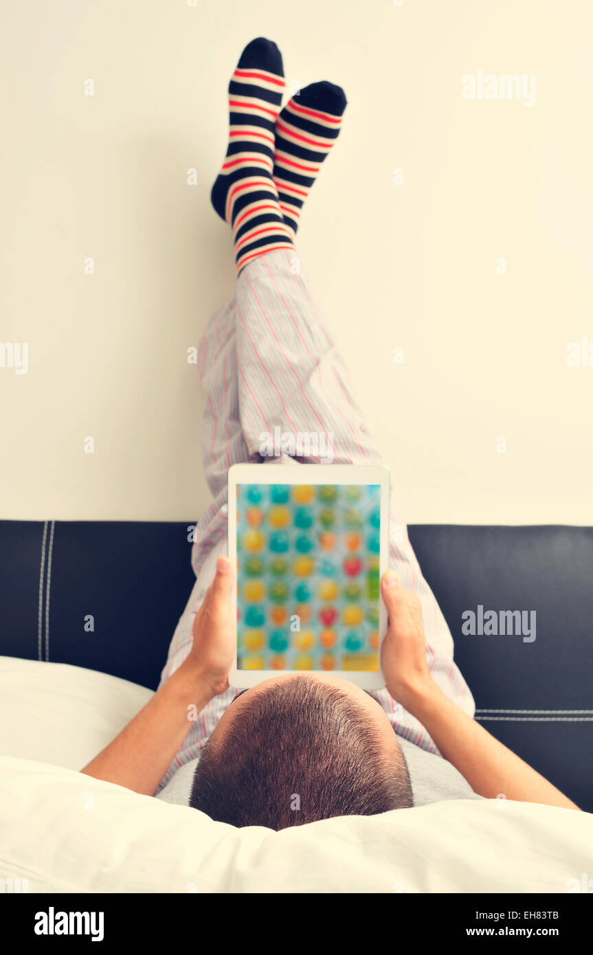 a young man in pajamas in bed using a tablet with his feet against the wall - Stock Image