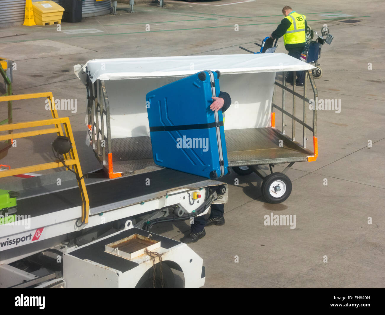 Baggage handler loading bike onto Ryanair flight at Manchester UK - Stock Image