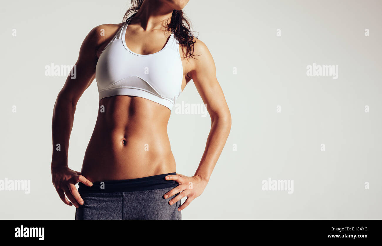 Close up of fit woman's torso with her hands on hips. Female with perfect abdomen muscles on grey background - Stock Image
