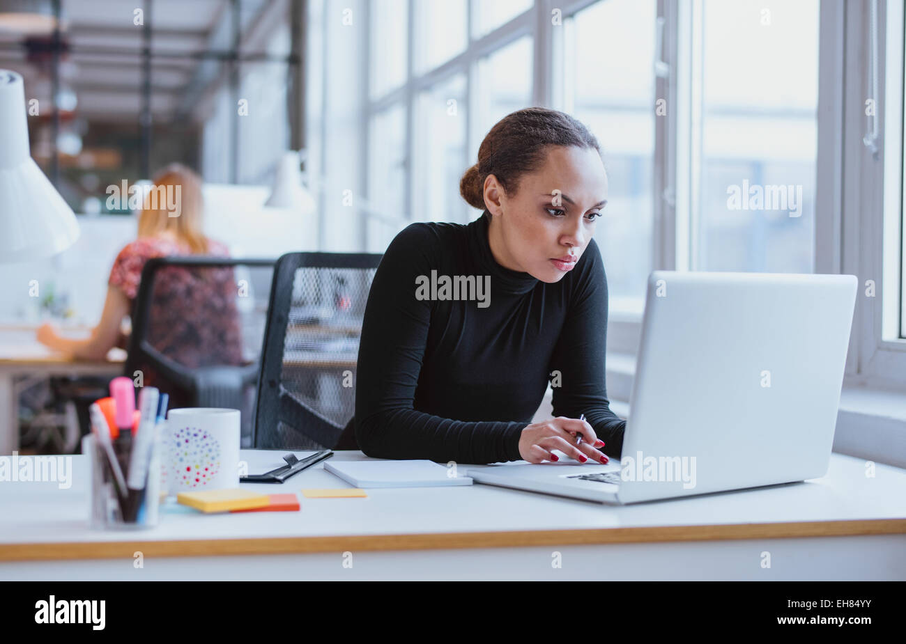Image of woman using laptop while sitting at her desk. Young african american businesswoman sitting in the office Stock Photo