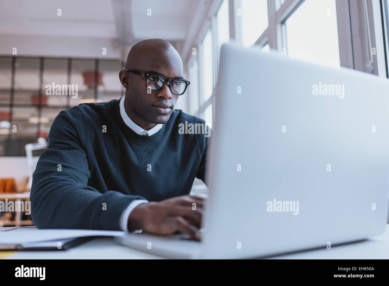 Young businessman working on his laptop in office. Young african executive sitting at his desk surfing internet - Stock Image