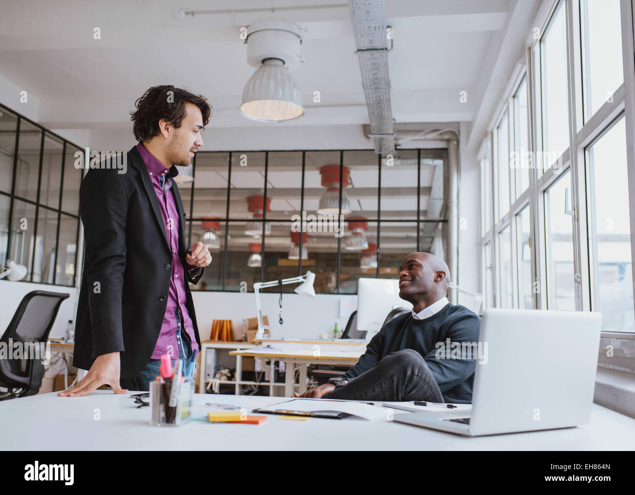 Two young office workers having a casual meeting at desk. Mixed race business people discussing work in office. - Stock Image