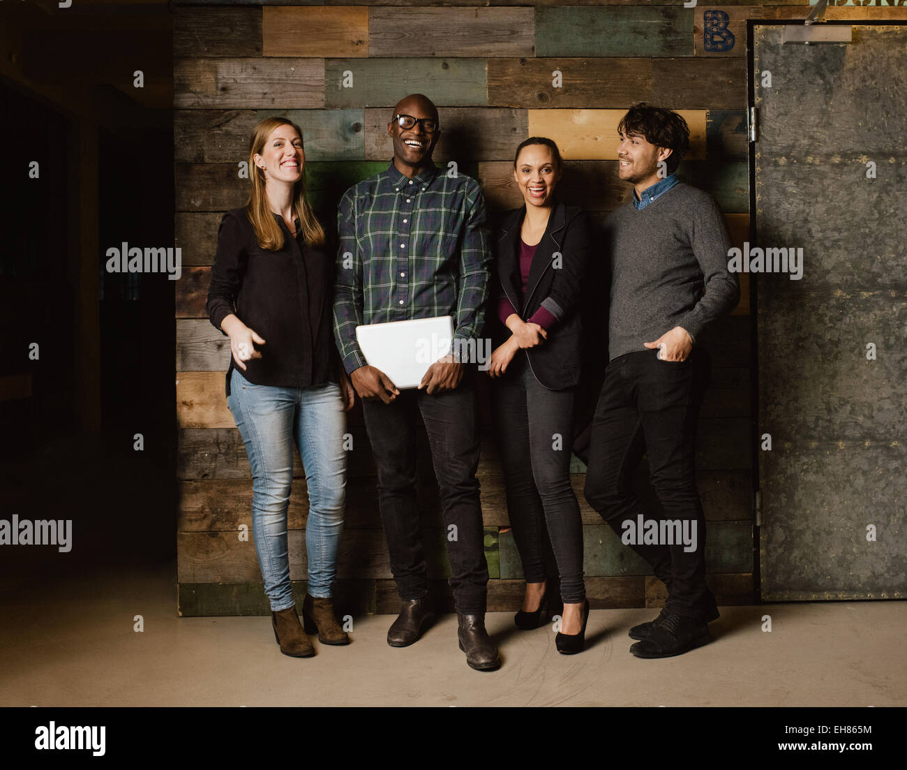 Portrait of young professionals laughing while standing together in office. Multi ethnic business team looking happy - Stock Image