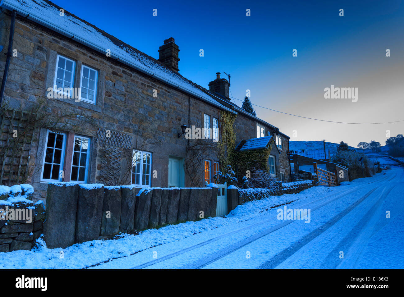 Stone cottages, on country lane at blue hour, fresh winter snowfall, Curbar, Peak District National Park, Derbyshire, - Stock Image