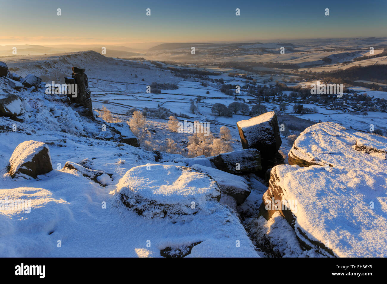 Snow on millstone lit by sunrise, Curbar and Baslow Edge with misty hills and wintry trees, Peak District, Derbyshire, - Stock Image