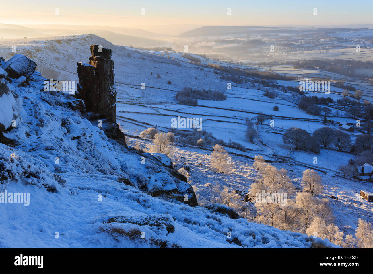 Curbar and Baslow Edge with misty Derwent valley and winter trees, Peak District, Derbyshire, England, United Kingdom - Stock Image