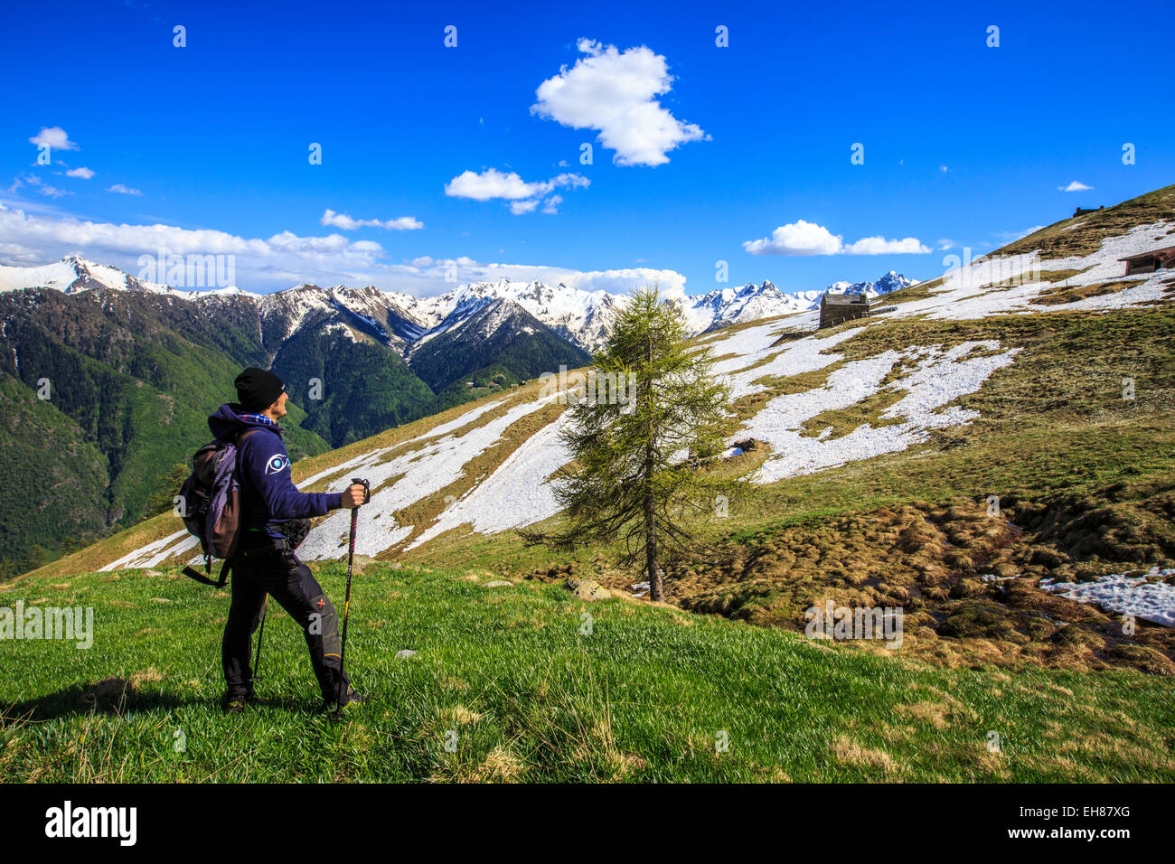 Hiker contemplating the landscape that can be seen from the Cima della Rosetta in the Orobie Alps in the spring, - Stock Image