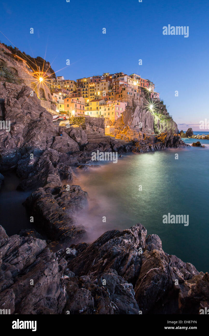 Blue hour in the little village of Manarola with its pastel coloured houses in the Cinque Terre National Park, Liguria, - Stock Image