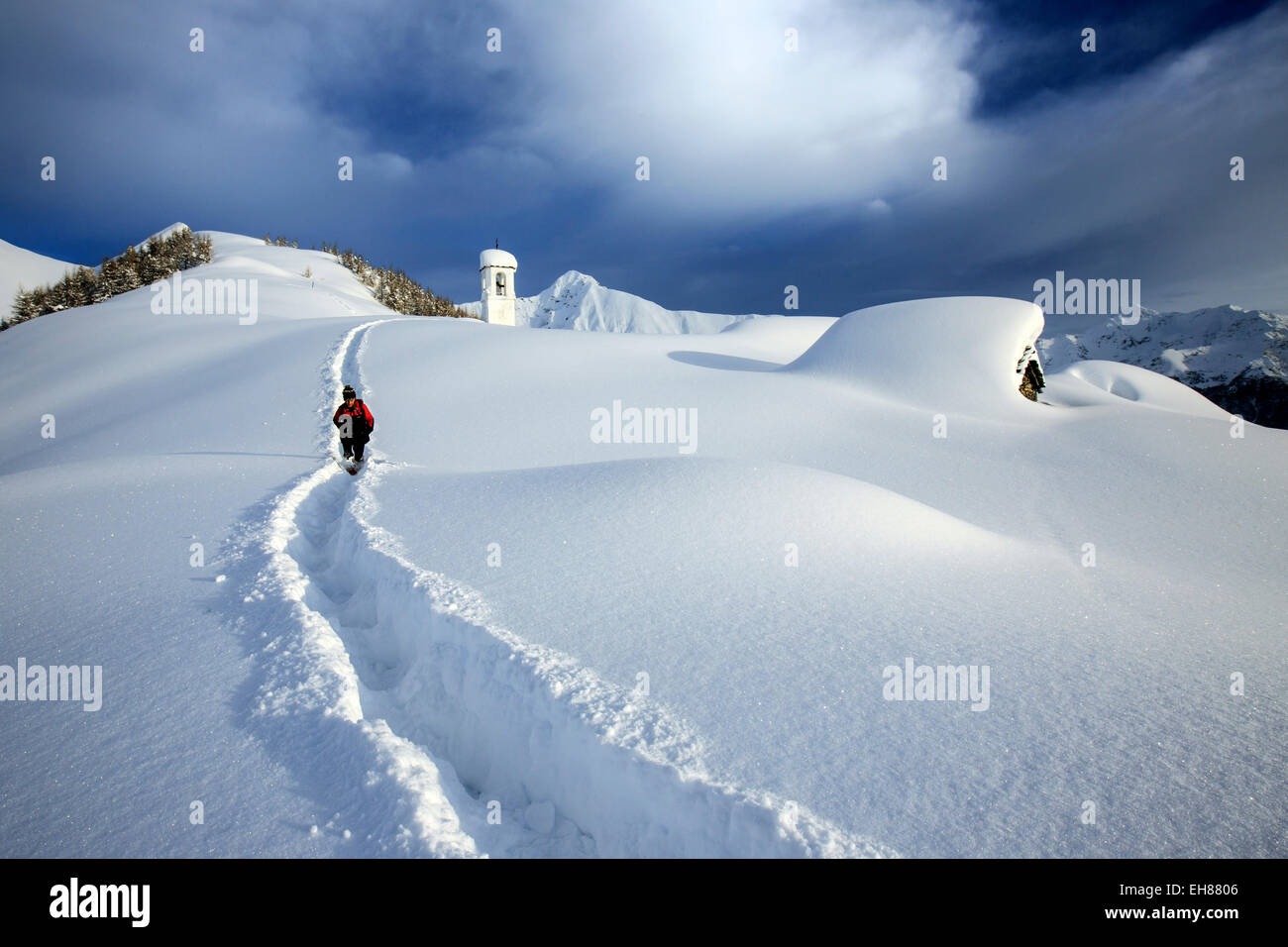 A solitary hiker leaving the little village at the Scima Alp covered in snow, Valchiavenna, Lombardy, Italy, Europe - Stock Image