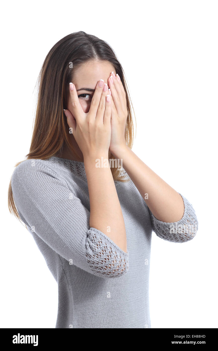 Embarrassed woman looking through her hands covering her face isolated on a white background - Stock Image