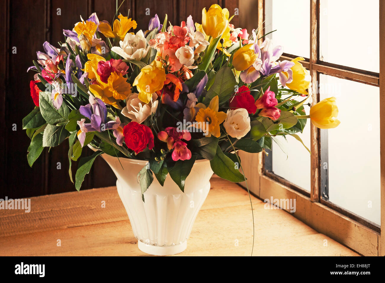 Colourful spring bouquet in a vase in front of a wooden wall by a window - Stock Image