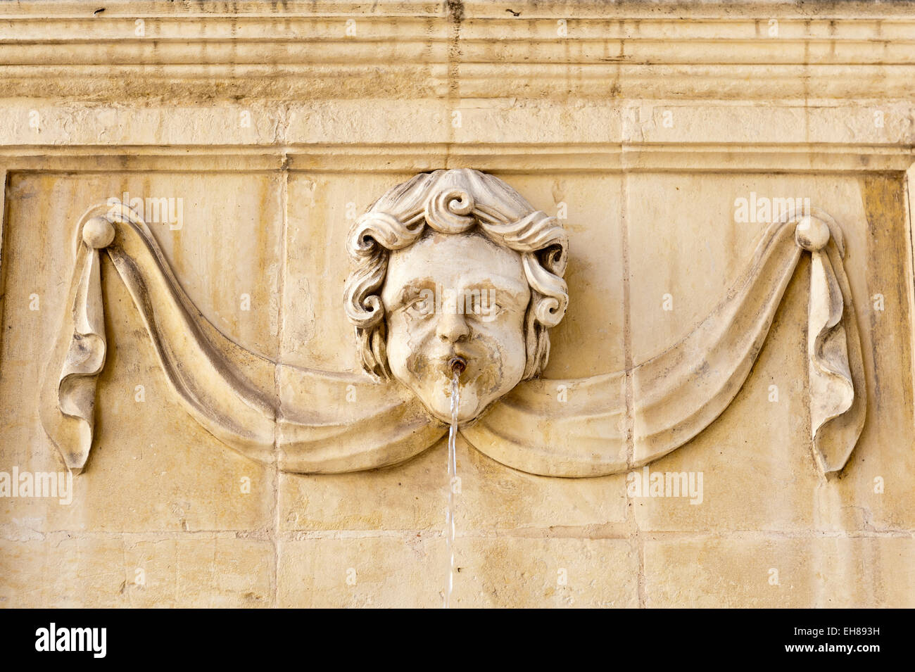 Baroque-style face on a fountain at St. John's Co-Cathedral, church of the Order of the Knights Hospitaller - Stock Image