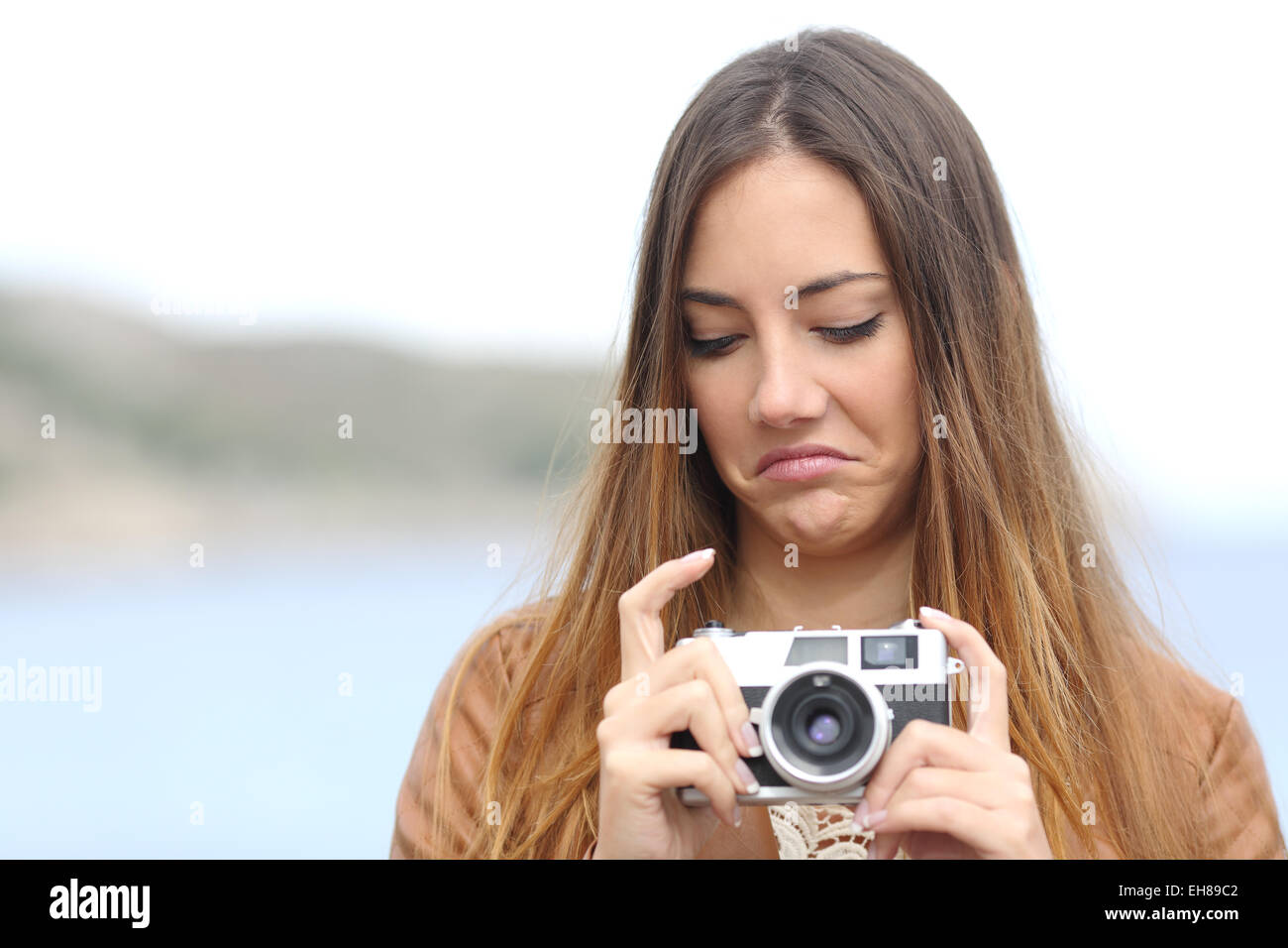 Upset photographer woman looking her old slr photo camera disgusted with the sea in the background - Stock Image