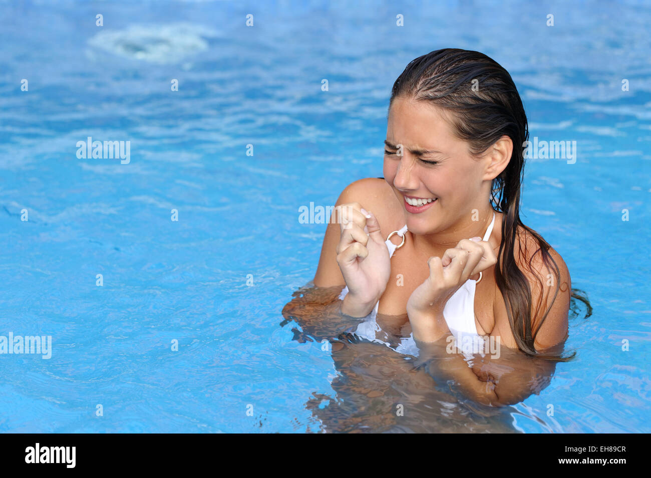 Woman complaints while bathing in a cold water of a swimming pool - Stock Image