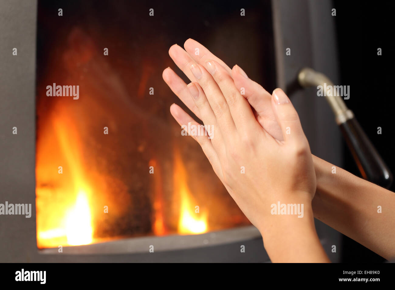 Woman rubbing hands and heating in front a fire place at home in winter - Stock Image