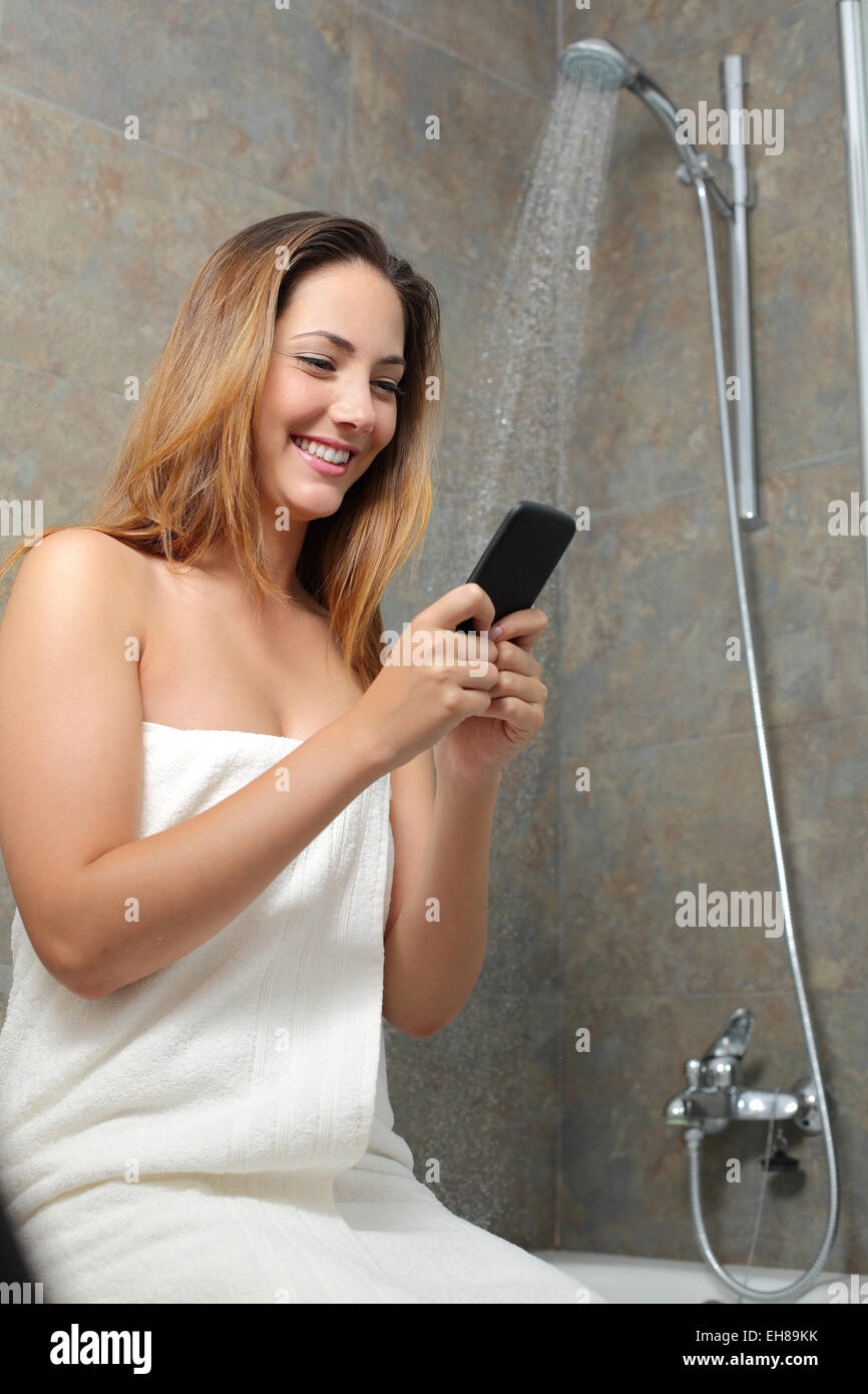 Woman texting on the phone in the shower while is wasting water - Stock Image