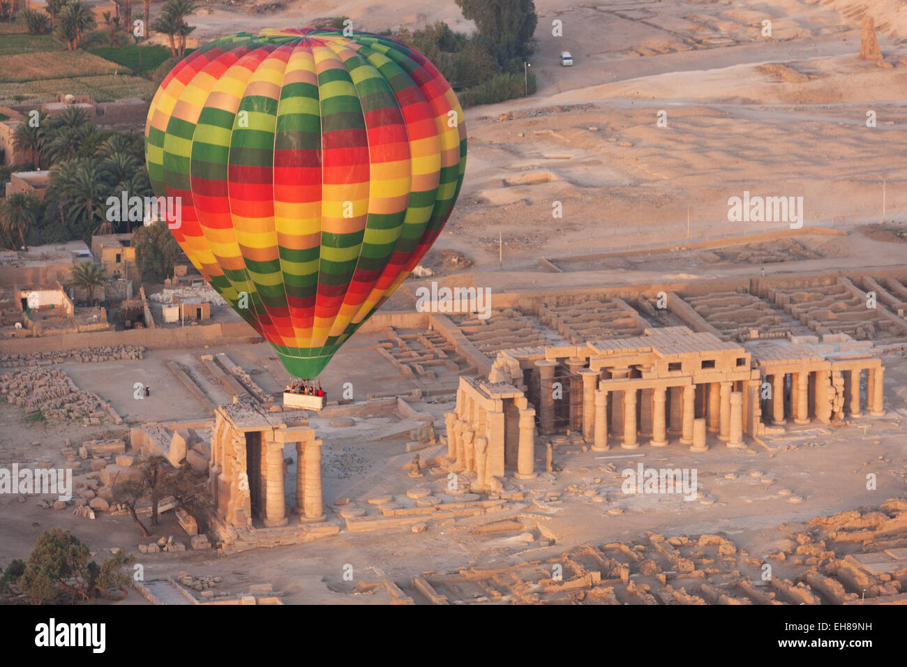 A hot air balloon flight over a ruined temple near Luxor, Thebes, Egypt, North Africa, Africa - Stock Image