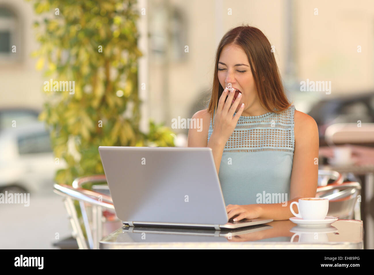 Tired woman yawning and working with a laptop in a restaurant during breakfast - Stock Image