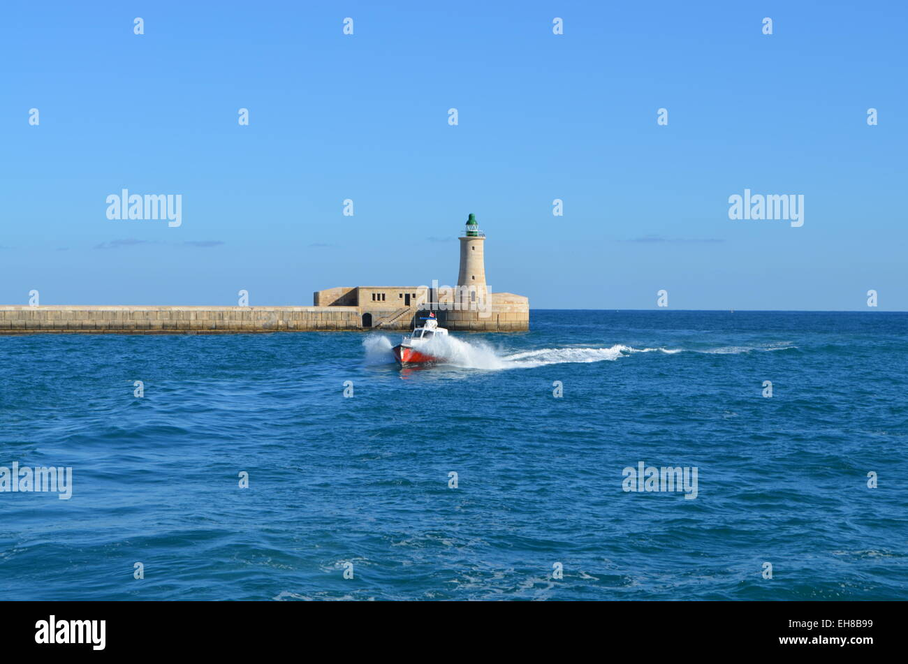 Valletta, Malta Harbour, Out to sea again and past the Harbour Lighthouse. - Stock Image