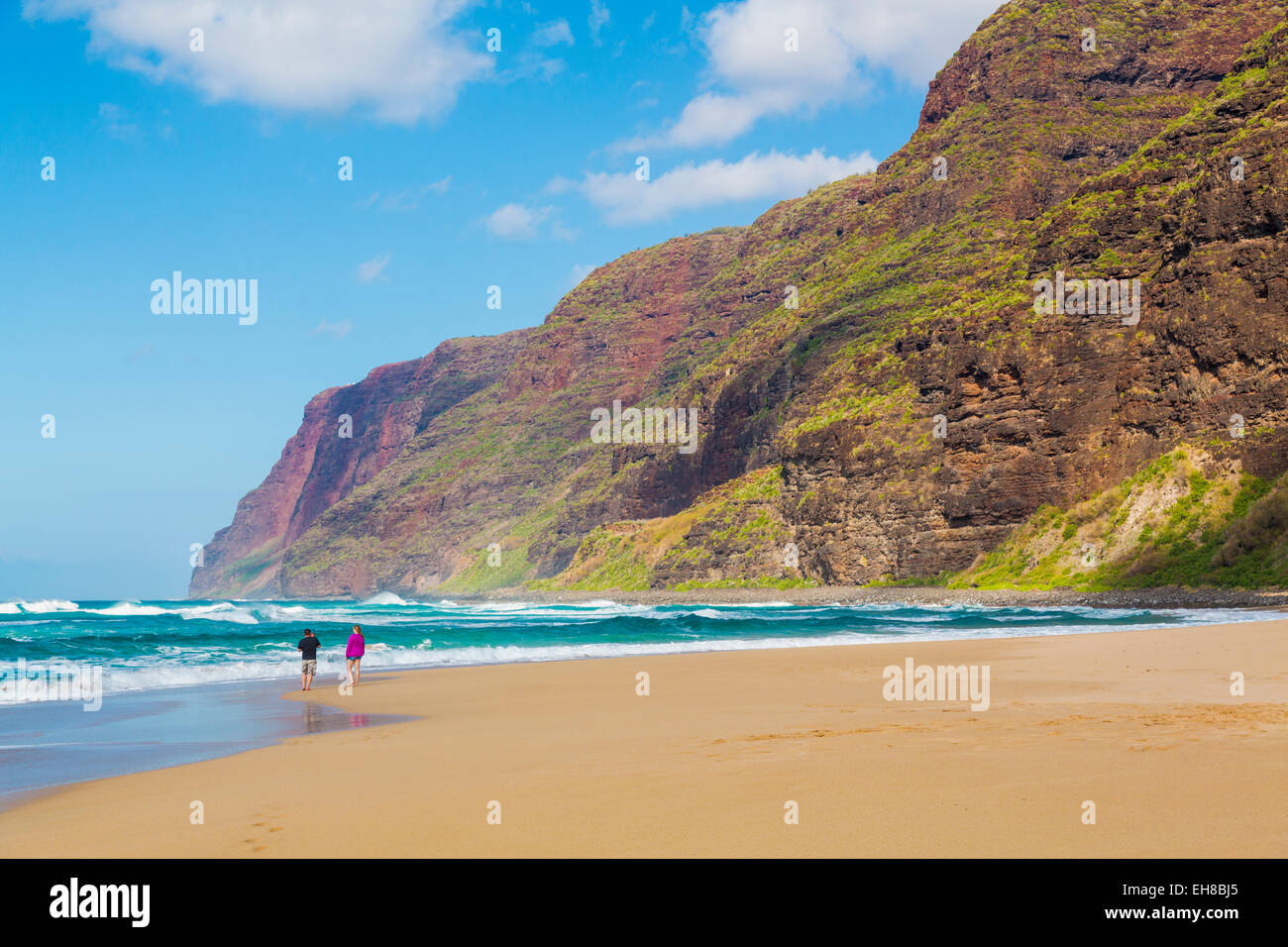 People walking along the sand in waves off the Polihale beach in Kauai, Hawaii - Stock Image
